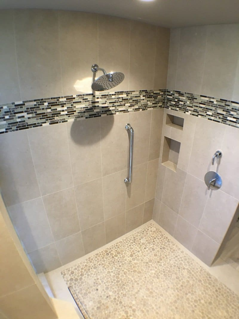 Shower with light grey tiling and a multi-colored accent strip of tiles