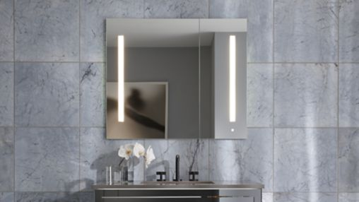 Medicine cabinet with lights built into the mirror, set against washed grey tile
