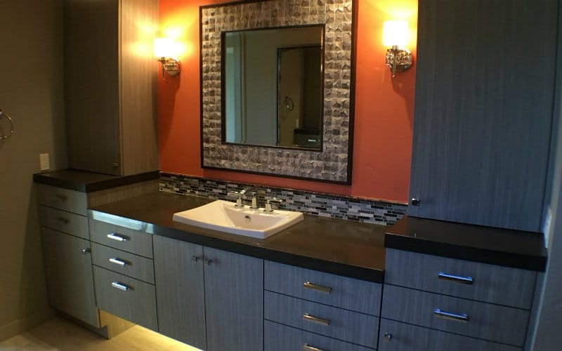 Vanity with grey cabinetry, tile, and a large mirror on a burnt orange wall