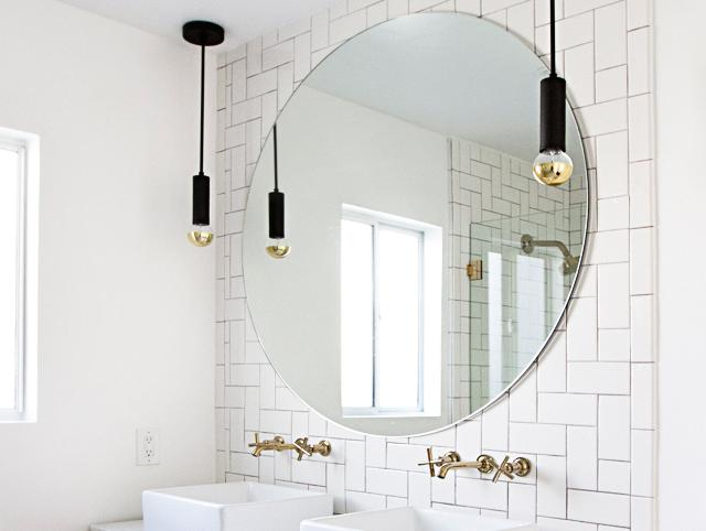 Large circle mirror with hanging modern lights and double vessel sink