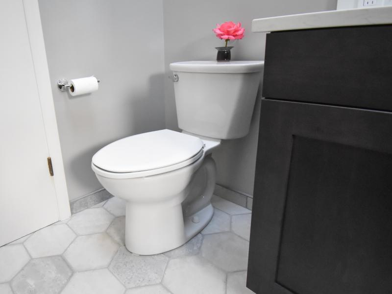 Toilet with flower on tank over grey hex tiles
