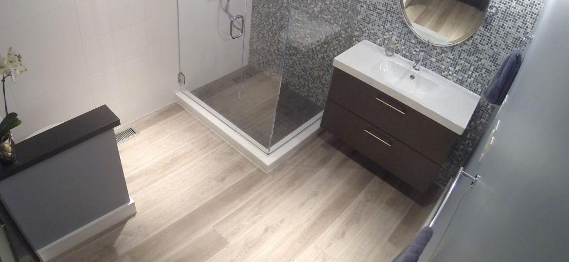 Remodeled bathroom with custom tile, new vanity, and glass shower