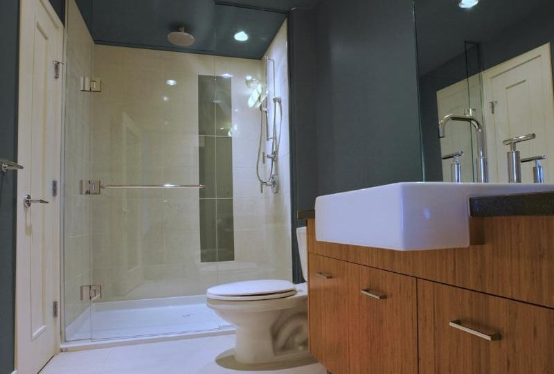 Glass doors on shower with ceiling mounted rain head shower and farmhouse sink
